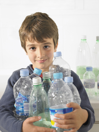 strive for: Young boy (6-8) holding an armful of recyclable plastic bottles, portrait
