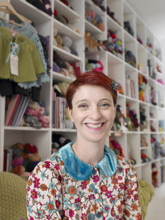 Woman sitting in craft shop, smiling, portrait, close-up LANG_EVOIMAGES