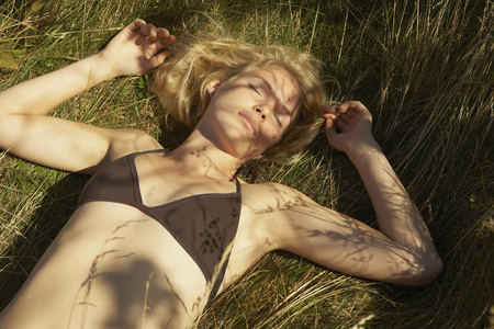 sweden resting: Young Woman lying in grass.