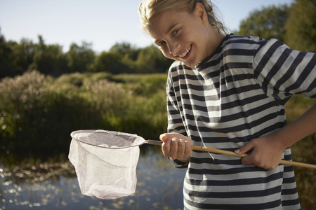 Young Woman by pond with fishing net. LANG_EVOIMAGES