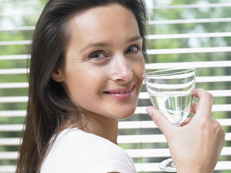 Woman standing by a window holding a glass of water smiling.