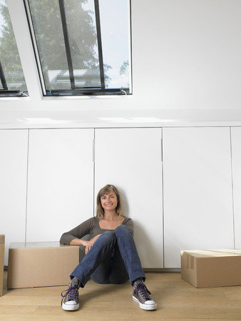 attics: Woman sitting with moving boxes in new home smiling. LANG_EVOIMAGES
