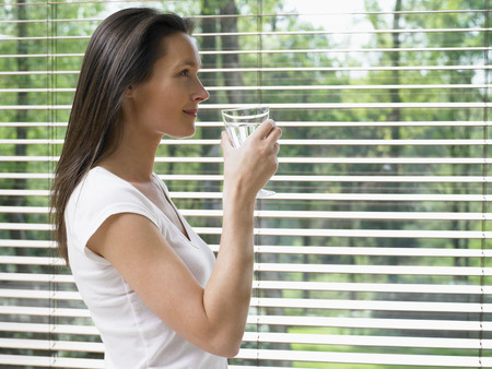window coverings: Woman standing by a window holding a glass of water smiling.
