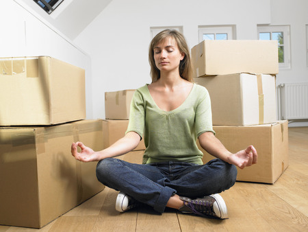 attic: Woman doing yoga with moving boxes around her.