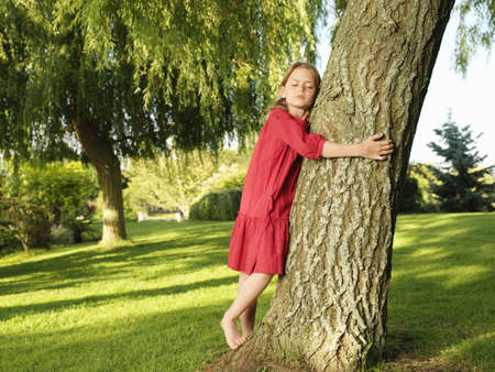 bashfulness: Young girl hugging tree