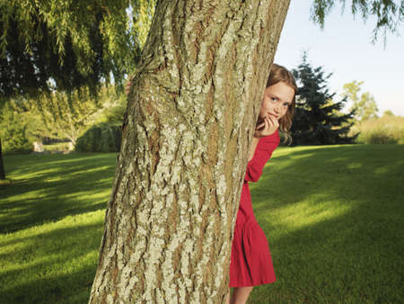 bashfulness: Young girl hiding behind tree LANG_EVOIMAGES