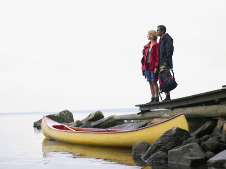 ruck sack: Couple standing on a dock near a boat.