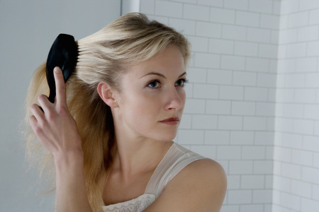 grooming: Portrait of a woman with a hairbrush.