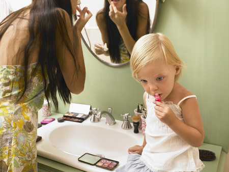 grooming product: Mother and daughter applying makeup.