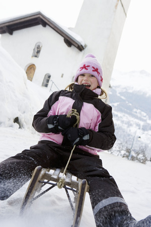 spewing: Young girl going down slope on sledge
