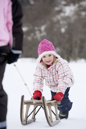 Young girl towed on sledge LANG_EVOIMAGES