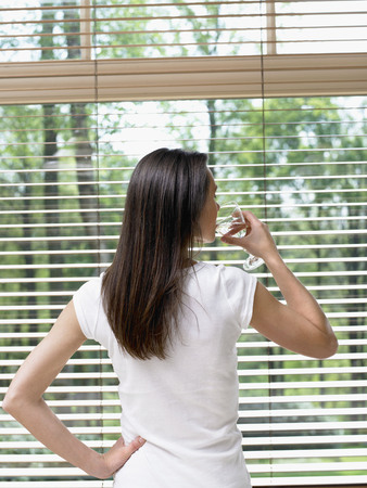 Woman standing by a window drinking a glass of water.