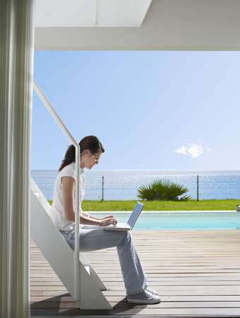 Female sitting outside with laptop LANG_EVOIMAGES