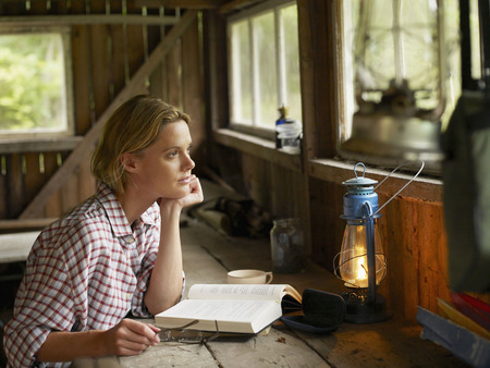 Woman sitting at a table in cabin with book and eyeglasses.