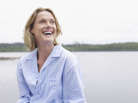 enjoys: Woman laughing outdoors by the water.