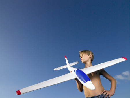 tweens: Young boy ready to send off an airplane.