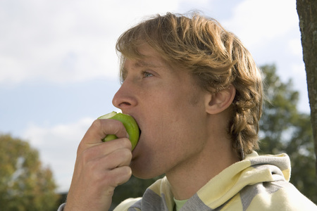 snacking: Young man eating apple.
