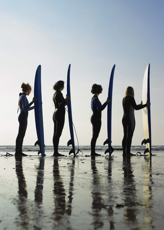blue waters: Four female surfers standing on a beach.