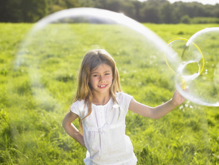 differential: Little girl making soap bubbles.