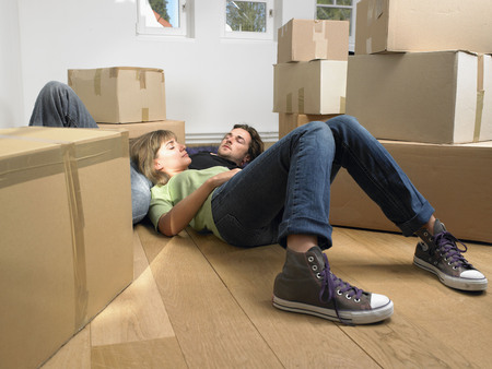 attics: Couple sleeping on floor with moving boxes around them. LANG_EVOIMAGES