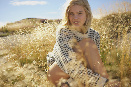 Young Woman Sitting in Long grass.