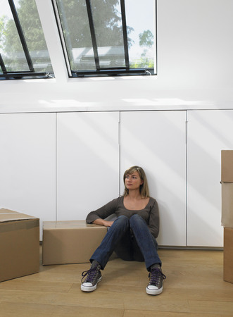 cardboard only: Woman sitting with moving boxes in new home. LANG_EVOIMAGES