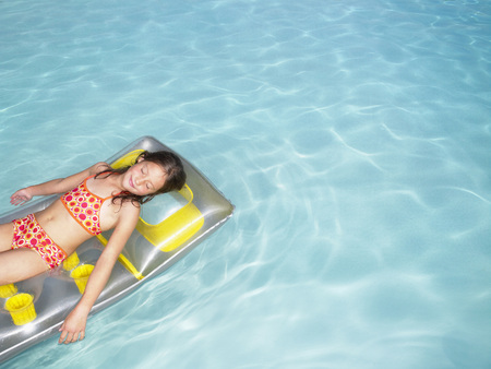 tot: Girl on air mattress in pool. LANG_EVOIMAGES