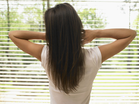 window coverings: Woman standing by a window stretching. LANG_EVOIMAGES