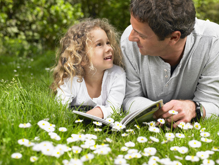 tot: Man and young girl lying in the grass reading and smiling.