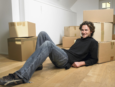 attics: Man lying on floor smiling with moving boxes around him.