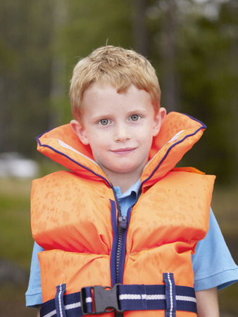 lifevest: Young boy in a life jacket looking at camera.