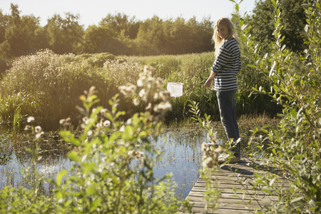 get away: Young Woman by pond with fishing net. LANG_EVOIMAGES