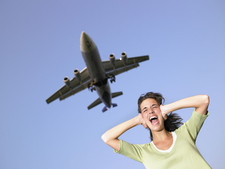 Woman covering ears and screaming with plane flying overhead. LANG_EVOIMAGES
