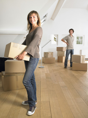 Couple moving into new home smiling. LANG_EVOIMAGES