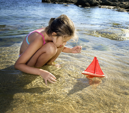Young girl with a toy sailboat at the beach. LANG_EVOIMAGES