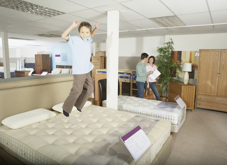 customer facing: Boy jumping on bed in furniture store.