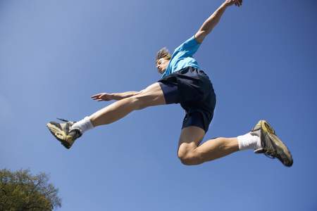 in low spirits: Young man jumping in sports kit.