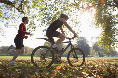 in low spirits: Cyclist riding mountain bike with jogger following.