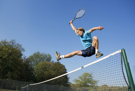 in low spirits: Young man with tennis racket jumping net. LANG_EVOIMAGES
