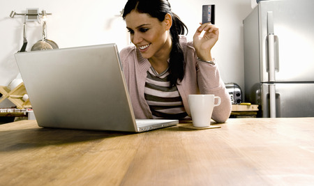 refrigerator: Woman looking at laptop with credit card.