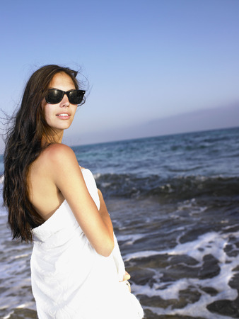 Woman standing in a towel at the beach. LANG_EVOIMAGES