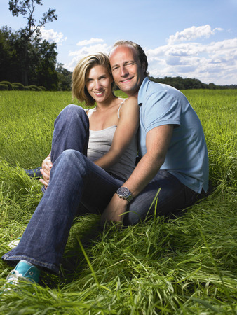 embraced: Couple sitting in a field.