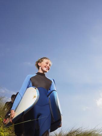 clear path: Female surfer walking through grass.
