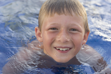 Young boy smiling in swimming pool.