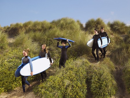 Five teenagers walking with surfboards .