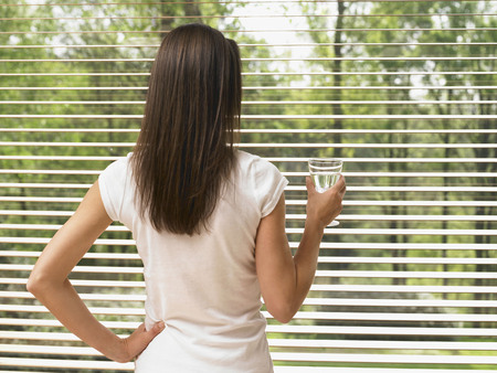 Woman standing by a window holding a glass of water.