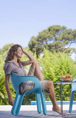 Woman on a wooden terrace by a pool LANG_EVOIMAGES