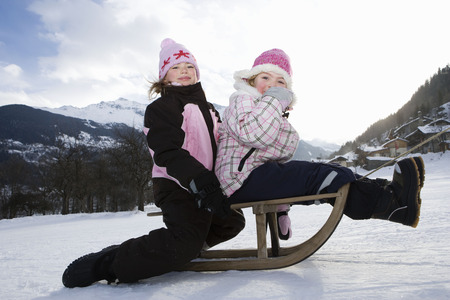 Girls towed on sledge in snow