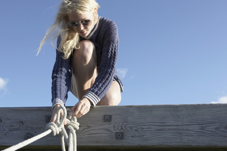 Young woman undoing ropes on jetty.