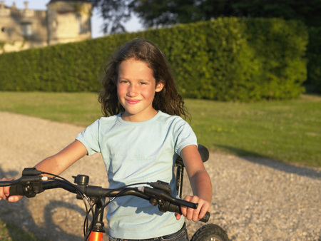 Young girl on bicycle looking at camera.